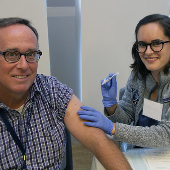 man getting a flu shot smilimg
