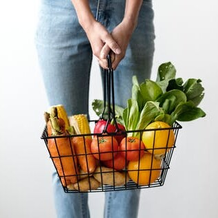 woman holding shopping basket loaded with vegetables